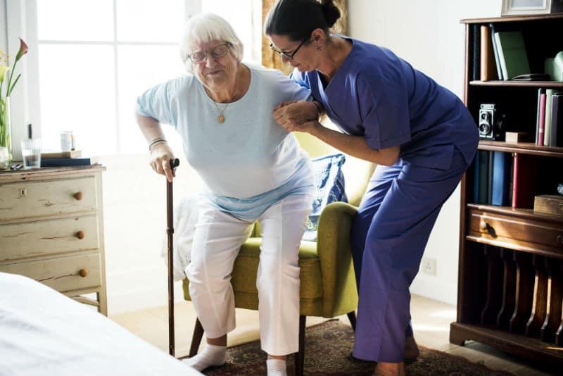 Accompagnatrice qui aide une vieille dame à se lever