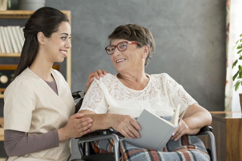 Aide-soignante avec une dame en fauteuil roulant