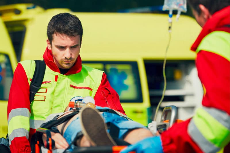 Ambulancier qui transporte un blessé