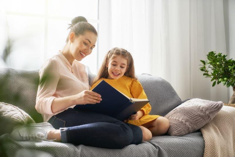 Garde d'enfant qui lit un livre à la maison