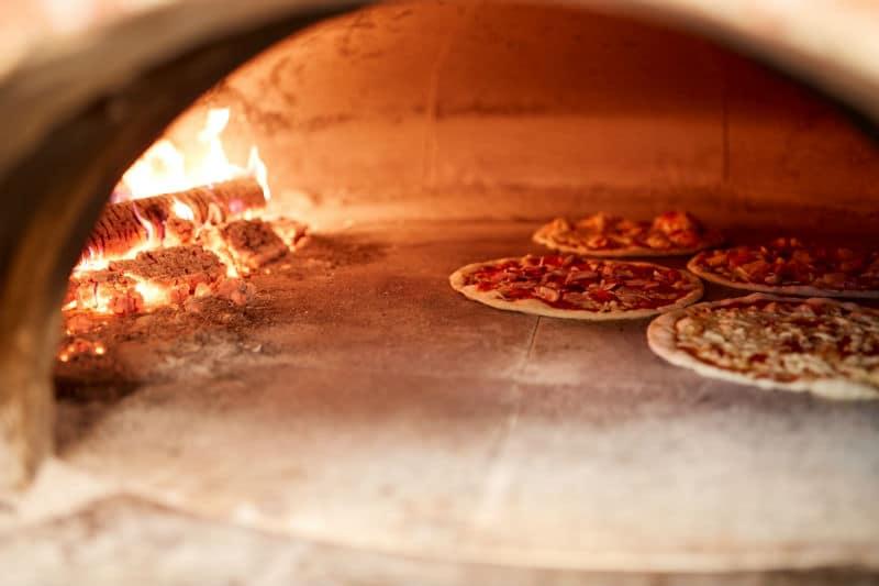 Pizza qui cuisent dans le four d'une pizzeria
