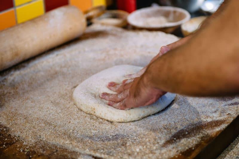 Pizzaïolo qui prépare de la pâte à pizza