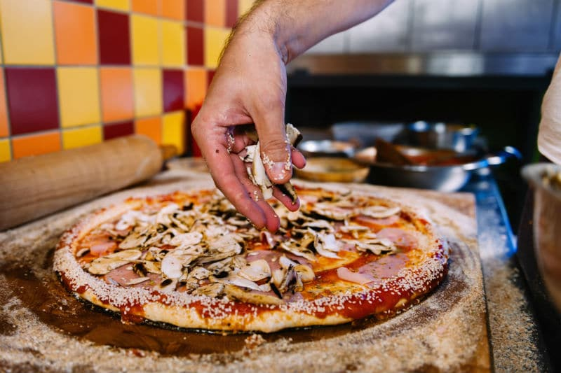 Pizzaïolo qui met des ingrédients sur une pizza