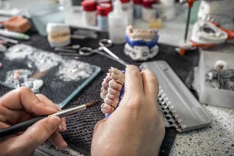 Prothésiste dentaire qui travaille sur des dents en céramique