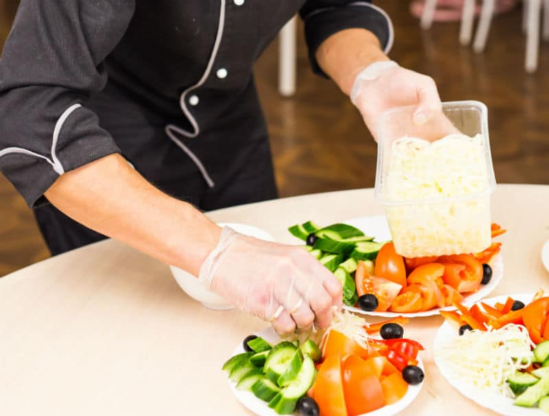 Agent de restauration collective qui prépare des assiettes