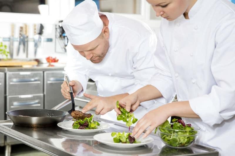 Commis de cuisine qui dressent des assiettes