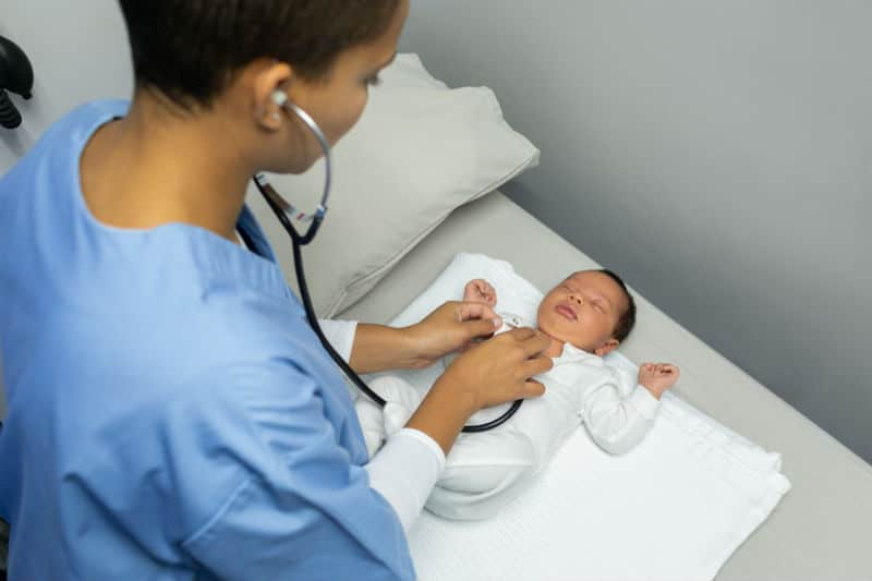 Puéricultrice qui ausculte un bébé